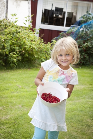 Happy child with a bowl of freshly picked berries Stock Photo - 17261041