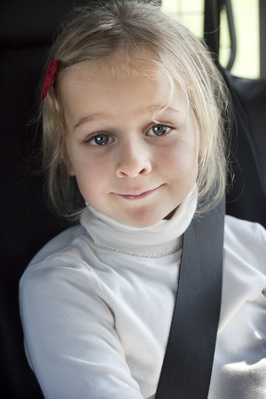 A smiling girl with seat betl in a car photo