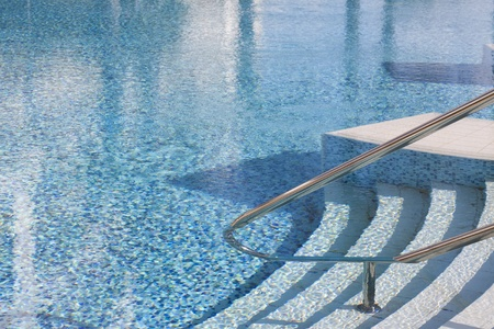Rails and stairs leading into a blue swimmingpool Stock Photo - 17269530