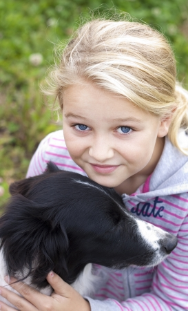 Girl looking at camera, hugging a dog photo