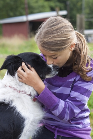 Girl caressing her dog, a border collie photo