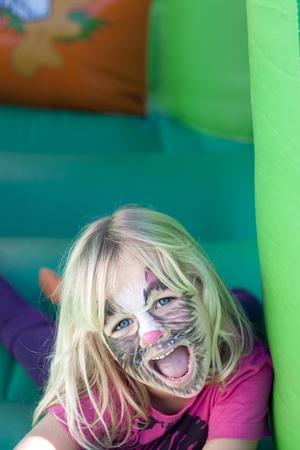 pintura en la cara: Una muchacha que hace una cara divertida, pintura de la cara como gato