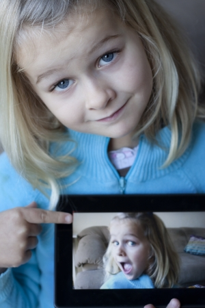 A cute girl holding a tablet which shows a blurred photo of herself Stock Photo - 17390763