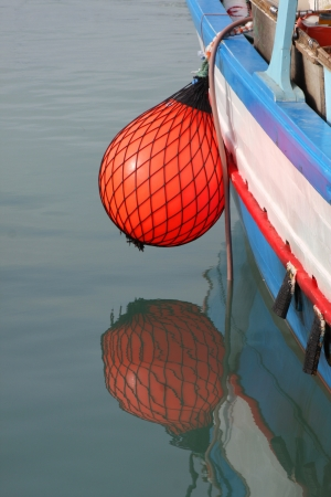 Bright red fender on side of a maltese fishing boat Stock Photo - 17624903