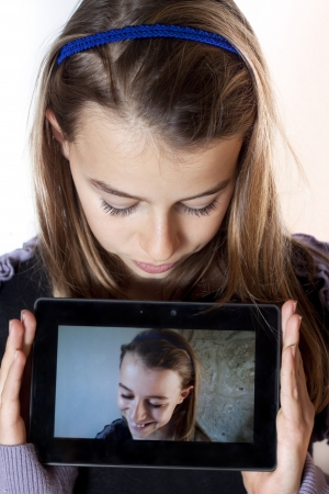 13: Young girl holding a tablet showing a photo of herself