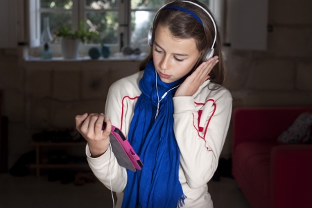kindle: A girl holding an ebook wearing headphones Stock Photo