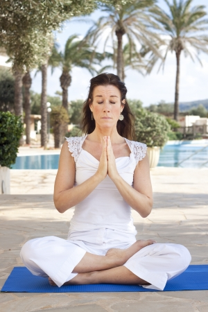 Middle aged lady sitting in a lotus yoga position photo