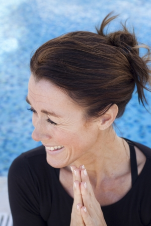 A middle aged laughing lady doing a yoga greeting, namaste Stock Photo - 17700424