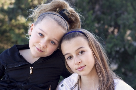 13 14 years: Portrait of two young sisters outside in a park