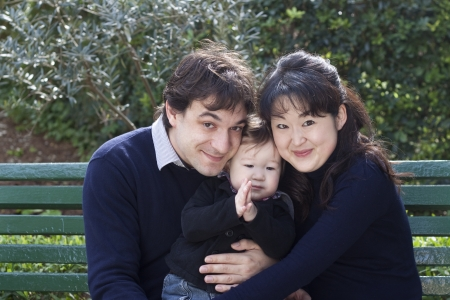 French father and Japanese mother with their baby boy in a park  Stock Photo