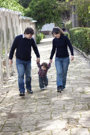 A mixed race family with asian mother and caucasian father, teaching their son to walk photo
