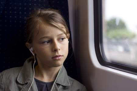 Girl with headphones on train or bus, looking out of window