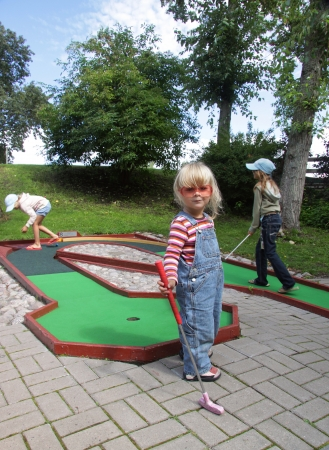 Three hillybilly looking kids playing miniature golf