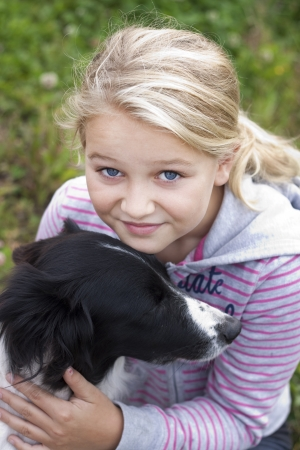 8 9 years: A beautiful young girl with her dog, looking at camera, Positive feeling
