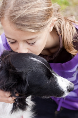10 to 12 years: Close up of a pretty girl hugging a dog.