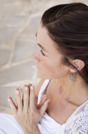 kundalini: Una signora maggiore che fa yoga, tenendo le mani pregando