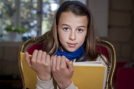 A young girl holding up a book, looking at camera, Real people, candid shot photo