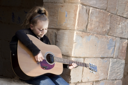 A girl learning or practicing on a musical instrument, a guitar. Space for text photo