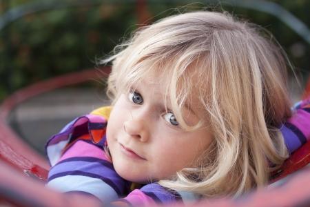 climbing frame: Una ragazza carina che riposa su un telaio di arrampicata in un parco giochi