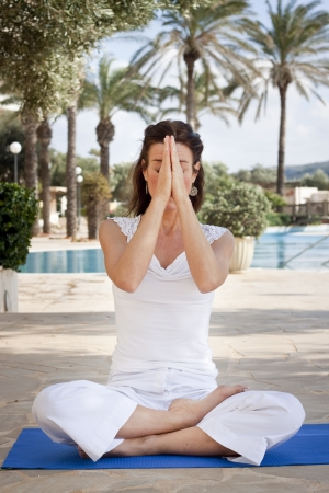 kundalini: Woman meditating in lotus position with eyes closing, holding up hands in namaste greeting