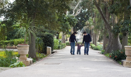 paternity: A baby boy of mixed race is walking with his parents in a colonial park