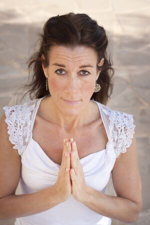 kundalini: Mature woman with hands together in namaste or prayer, looking at camera