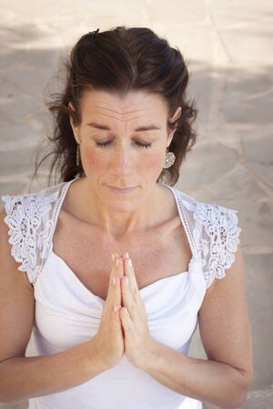 Mature woman with hands together in namaste or prayer, eyes closed photo
