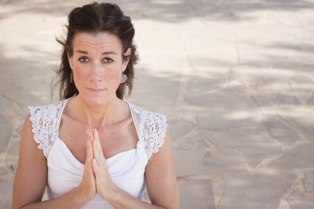 Mature woman with hands together in namaste or prayer, looking at camera  Space for text photo