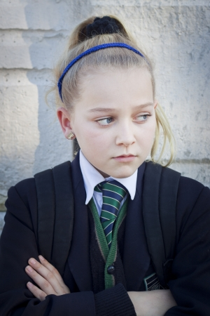 An upset teenager at school, looking away from camera  Candid shot, real people