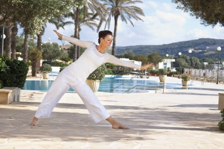 Elegant mature woman doing yoga in hotel resort Stock Photo - 19875133