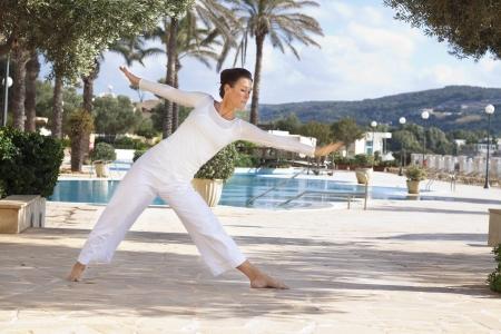 Elegant mature woman doing yoga in hotel resort photo