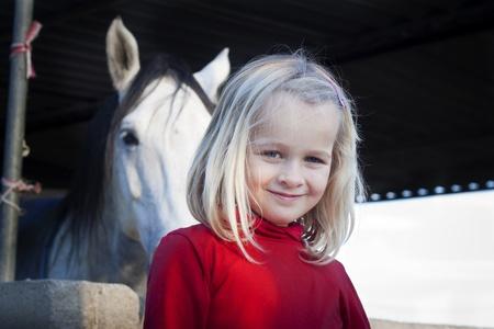 feeling positive: Un ni�o peque�o que se coloca delante de su caballo, mirando a la c�mara, sentimiento positivo Foto de archivo
