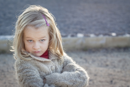 arrogant teen: Cheeky little girl with attitude looking at camera Stock Photo