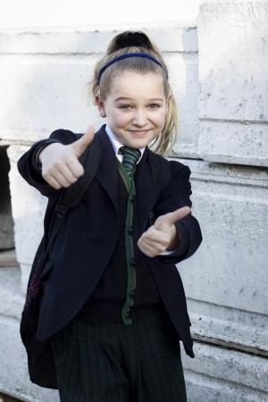 feeling positive: Ni�a de la escuela con el uniforme haciendo pulgares, sentimiento positivo