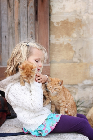 6 year old child holding two ginger cats photo