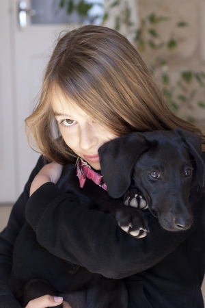 Teenager with cute black dog, looking at camera, Candid shot, real people