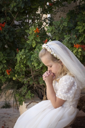 innocense: A young child praying during her first holy communion