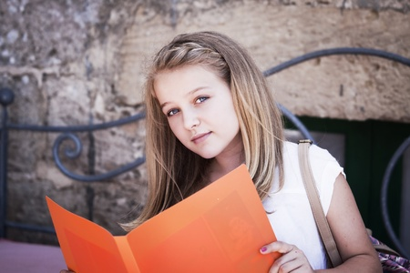 blonde teenager: A teenager reading from a file, looking at camera, positive feeling, candid shot