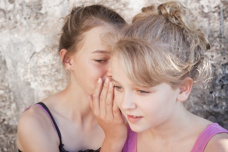 confide: Two teenage girls whispering secrets Stock Photo