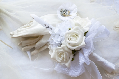A first holy communion candle with flowers, gloves and medal
