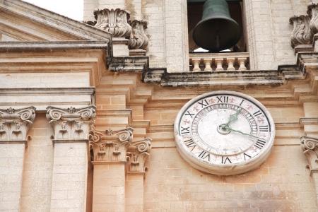 catholic mass: Close up of a church clock and church bell on a Maltese church
