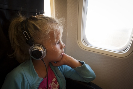 A little girl with headphones looking out of the window of an airplane