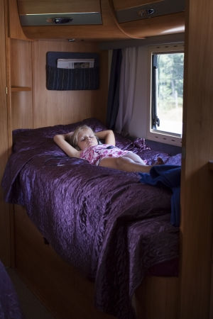 A girl sleeping in a bunk bed inside a moving trailer photo