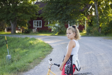 12 13 years: An alone girl looking upset on a bicycle in a rural area in Sweden