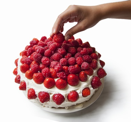 cake pick: A layered sponge cake decorated with strawberries and raspberries with a hand picking of one berry. Isolated on white