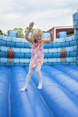 A 6 year old girl having fun on a bouncy mat