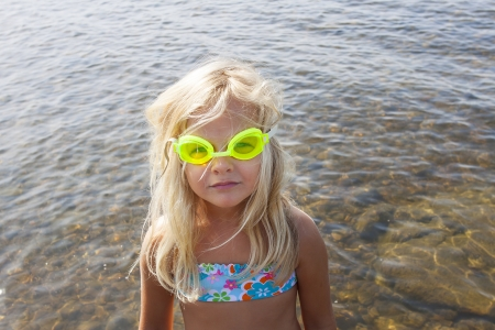 A little girl with yellow goggles looking at camera photo