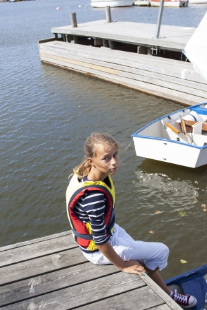 A gril sitting on a yetti with her optimist sailing boat photo