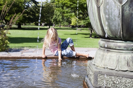 gothenburg: A young girl sitting on the edge of a fountain playing with the water