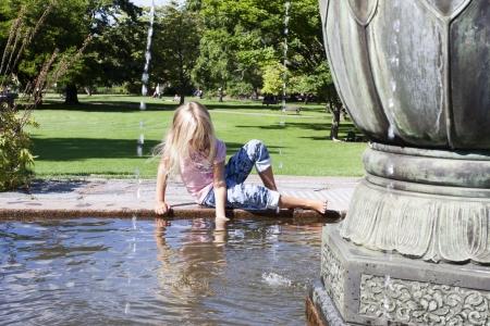 niños jugando en el parque: Una niña sentada en el borde de un juego fuente con el agua